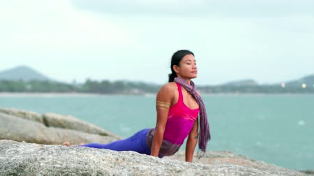 trecho : Yoga woman exercising hero pose, cobra pose and dog pose on beach Vídeos