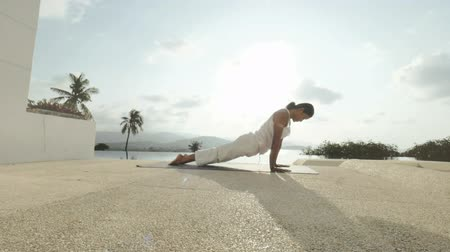 cobra : Sport woman practicing yoga exercises on outdoor terrace with panoramic view Stock Footage