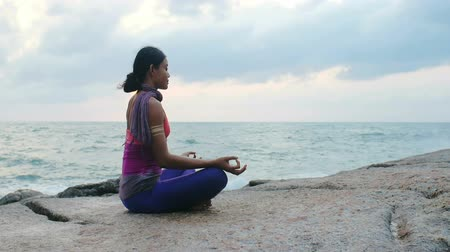 felvilágosodás : Young woman meditating during yoga practice on beach outdoo Stock mozgókép