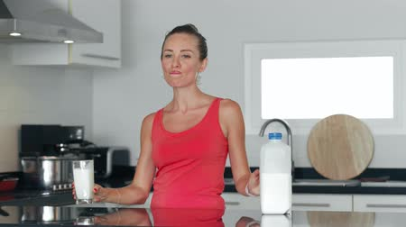 cálcio : Healthy woman drinking milk from glass on kitchen and putting milk bottle in fridge Vídeos