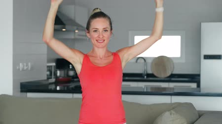 yetiştirmek : Smiling woman raising hands up during morning workout in home