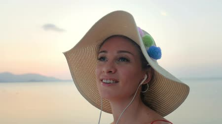 wearing earphones : Attractive woman singing while listening music on headphones. Stock Footage