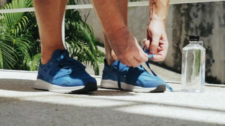 getting ready : Athlete ties up shoelaces blue sneakers. Stock Footage