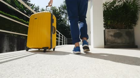 кроссовки : Tourist leaving modern apartment with a yellow suitcase.