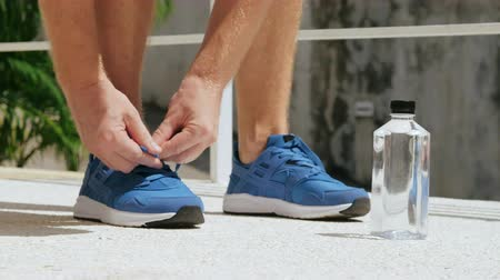 willpower : Close up of man tying running shoes.