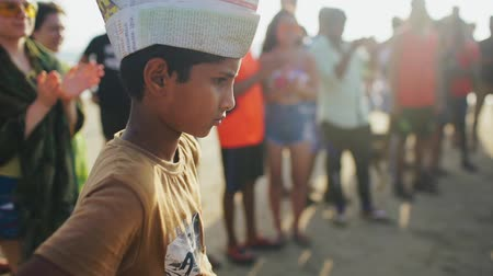descontente : Serious Indian boy watching performance on the beach