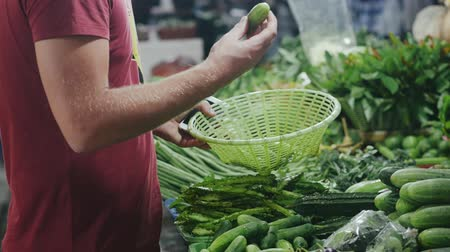 buying food : Buyer choosing vegetables and putting into the basket.