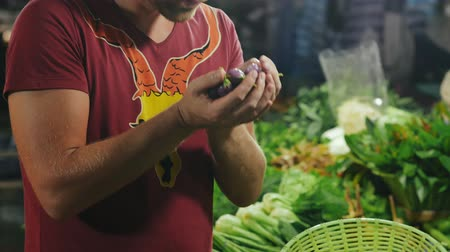 zöldségbolt : Tourist selecting vegetables and sniffs them at the farmers market.