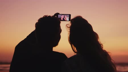 fondness : Back view of couple in love taking selfie