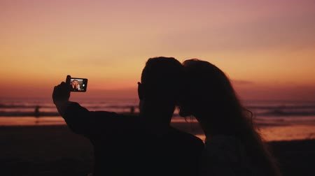 fondness : Lovely couple sitting on sea shore and making selfie Stock Footage