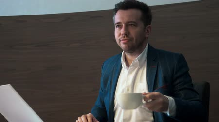 oblek : Handsome man drinking coffee from cup sitting at table in business office