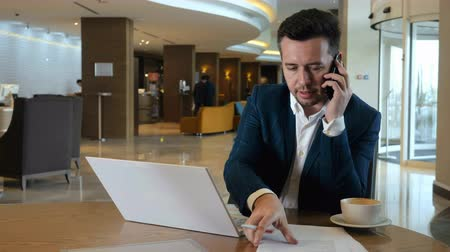 lobby : Man working on notebook and calling by smartphone during business trip in hotel