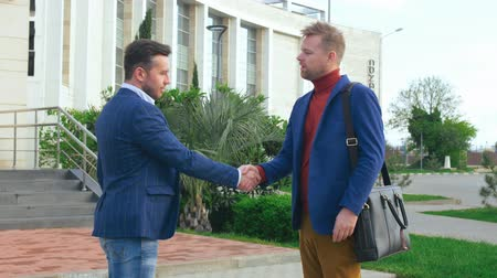 işlenmiş : Two promising young businessmen greeting each other with a handshake