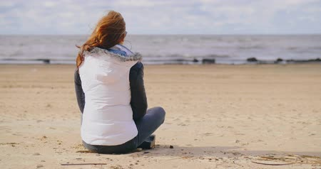 looking distance : Young girl sits on the beach in the cold autumn