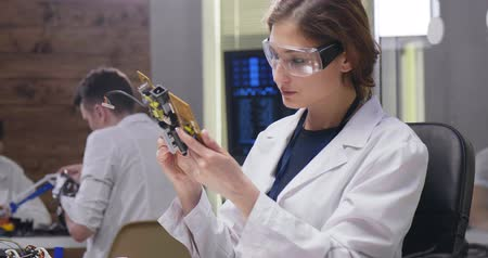 učit se : Portrait of caucasian female engineer examining robot detail