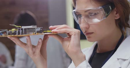 repairer : Close up of female electronics engineer examining motherboard