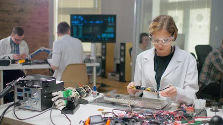 faculty : Portrait of young woman examining motherboard