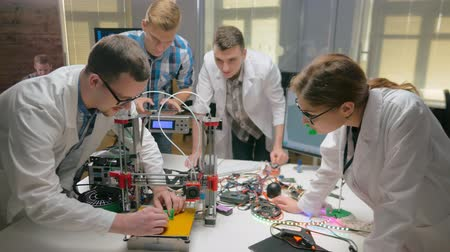 getting electricity : Group of engineers getting toy robot from 3d printer Stock Footage