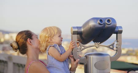 binocular : Mother holds daughter to look at view of the city Stock Footage