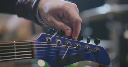 headstock : Rock musician tuning his guitar at rehearsal Stock Footage