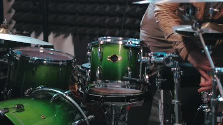 rehearsing : Musician in sunglasses tuning drum set