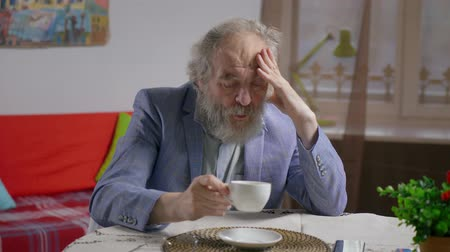 顔写真 : Portrait of depressed bearded entrepreneur suit drinking tea in cozy apartment.