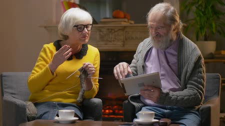 fed : Senior man and old age woman watching and discussing video on screen of tablet computer. Stock Footage