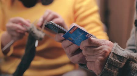 elderly care : Close up of pensioner holding credit card and smartphone.
