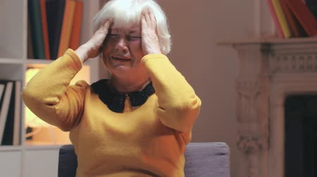 dor de cabeça : Portrait of senior woman suffering and crying in pain. Stock Footage