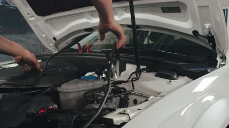 kapasite : Mechanic man measuring voltage on car battery in auto service. Car servicing