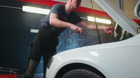 capacidade : Auto service worker checking voltage on car battery. Car service station