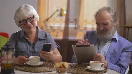 fizet : Elderly couple drink tea in their dining room sitting at a table with gadgets