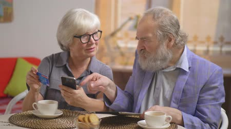 fizet : Charming couple is advised how to pay with a credit card from the smartphone Stock mozgókép