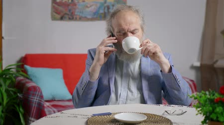 realty : Retired man talking on phone while sitting over a cup of tea in the living room Stock Footage