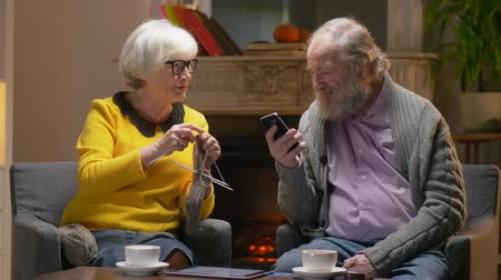 realty : Elderly man looks social networks in a smartphone next to his cute elderly wife Stock Footage