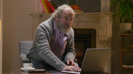 чат : Retiree man types with one finger on laptop and sits in his country warm cottage Стоковые видеозаписи