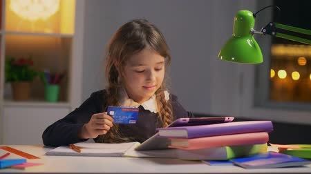 easily : Portrait of little girl typing on tablet number of credit card