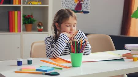 the conception : Little pretty girl with pigtails sitting at desk Stock Footage