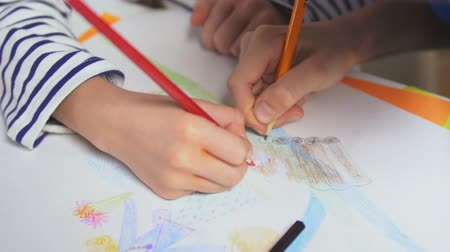 interactive table : Two hands of children drawing picture using pencils