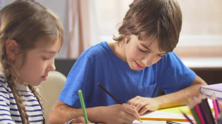 határozza meg : Brother and sister drawing with pencils at the desk in the nursery. Stock mozgókép