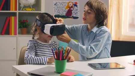 elsődleges : Little girl putting on virtual reality glasses Stock mozgókép