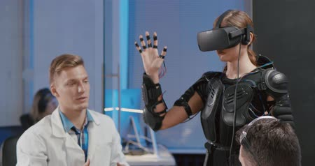 тестирование : Woman testing a VR helmet under the supervision of engineers. Стоковые видеозаписи