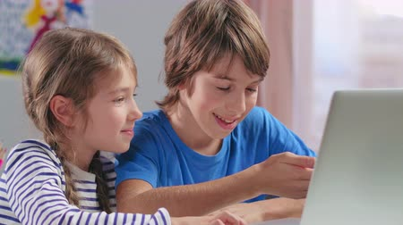 изобретение : Boy and girl watching cartoons on laptop computer
