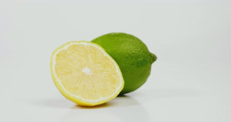 unpeeled : Picture of lime and half a lemon isolated on white background Stock Footage