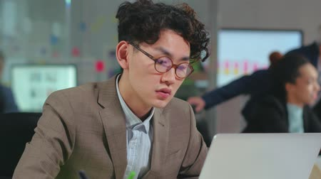 Young concentrated asian programmer in glasses