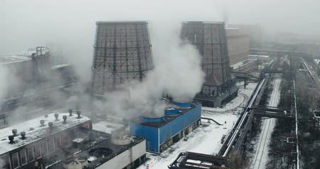 Aerial view - operating cooling towers at the plant with steam coming out