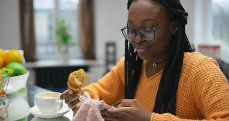 Beautiful african girl drinking coffee with croissant and chatting on phone