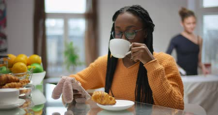 African girl has Breakfast and looks news of social network in phone