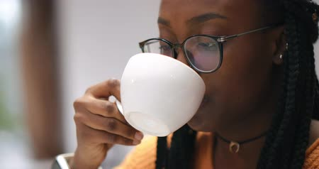 Portrait of beautiful African girl with glasses drinking coffee cappuccino