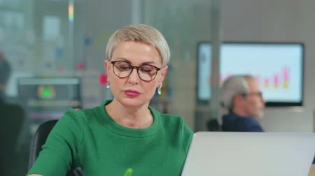 iş istasyonu : Attractive mature caucasian businesswoman working on laptop
